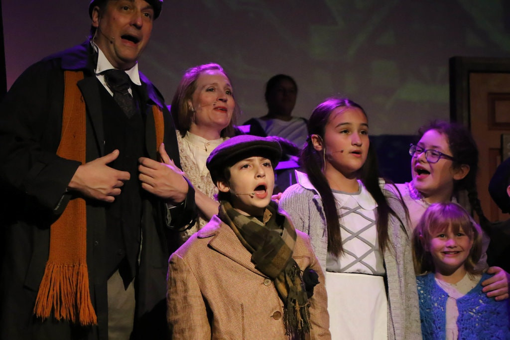 Mike Mazur as Bob Cratchit, Jonathan Rizzo as Tiny Tim, and others in Scrooge the Musical