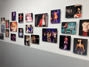 Photos hung on the wall of youth actors performing in musicals and plays